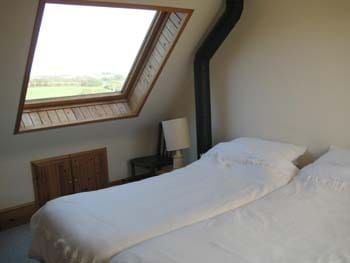 Top bedroom overlooking the green at the front and fields down to the sea at the back, with shower ensuite