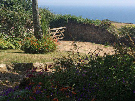 View of the garden and the sea from Foss self-catering holiday cottage in East Prawle, South Devon